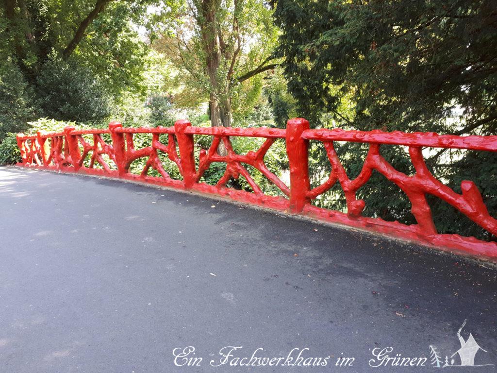 Ein Brückengeländer in einem Park in Breda, ganz in Rot, passend zum Redhad Day
