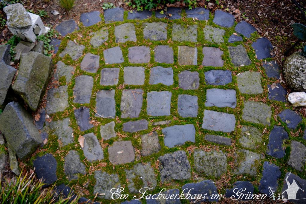 Gartenwege führen von einem kleinem Platz weg.