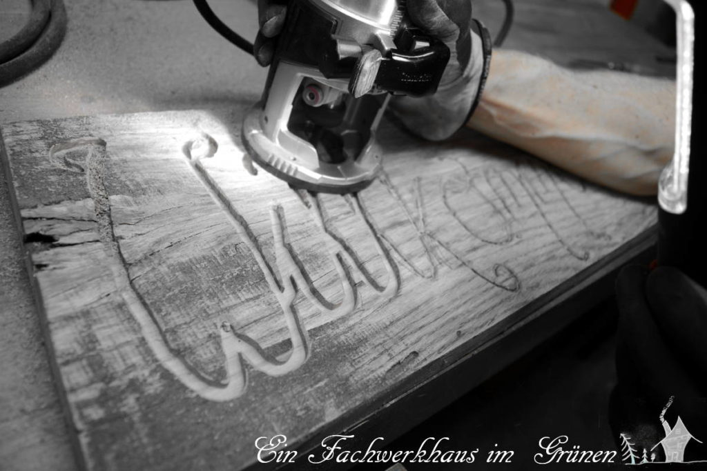 Mit der Oberfräse werden die Buchstaben in Holz gefräst.
