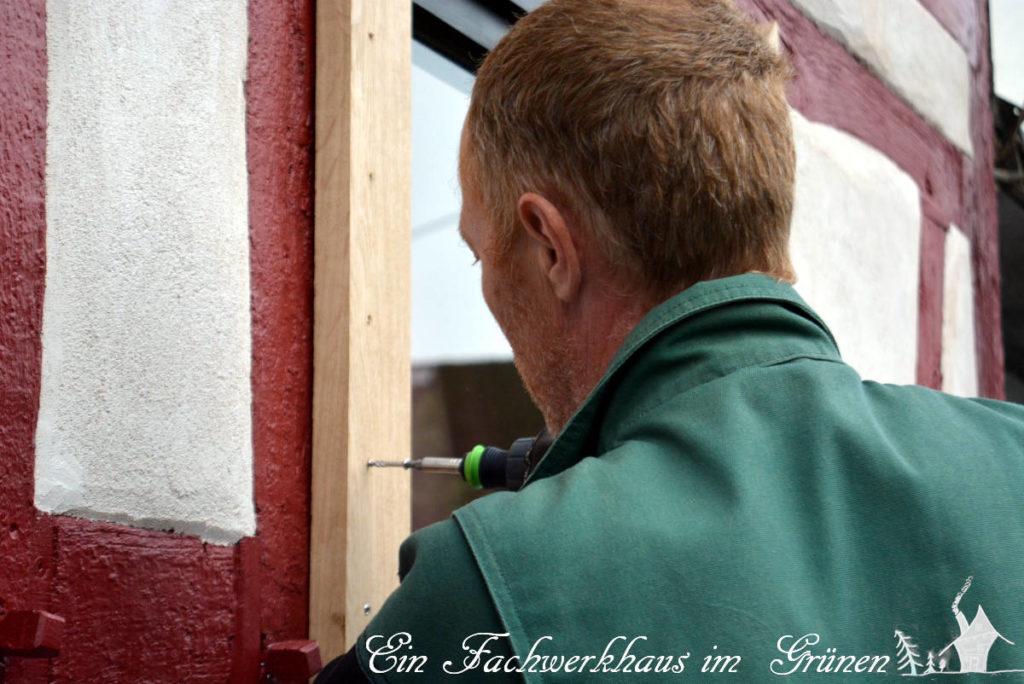 Nach dem Verputzen des Fachwerks werden die Fenster eingefasst.
