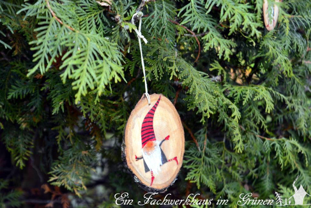 Ein Weihnachtszwerg an einem Lebensbaum in unserem Garten.